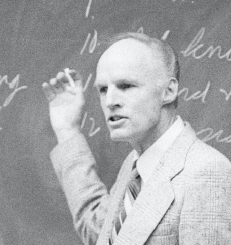 Truman Madsen teaching at a chalkboard.