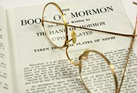 A pair of glasses sitting atop an open Book of Mormon