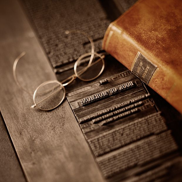 An old copy of the Book of Mormon sitting on a printing press next to a pair of spectacles