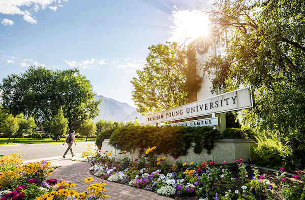 A sunlit, flower-filled photo of the Brigham Young University entrance sign.