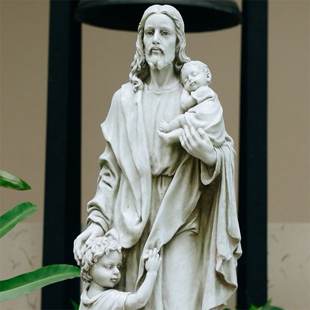 Statue of Jesus Christ holding a child, showing His great love for all humankind.