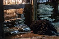 A nun bows in worship on holy ground near a row of candles in the Church of the Holy Sepulcher in Jerusalem.