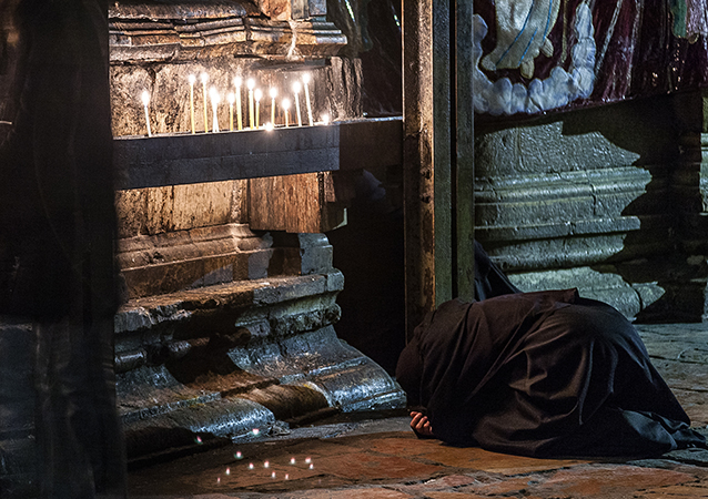 A nun bows in worship near a row of candles in the Church of the Holy Sepulcher in Jerusalem.