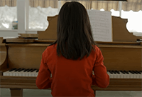 Young girl playing the piano, signifying the relationship between God's grace and a parent providing music lessons for their child.