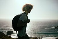 Young man with a backpack looking out at the ocean.