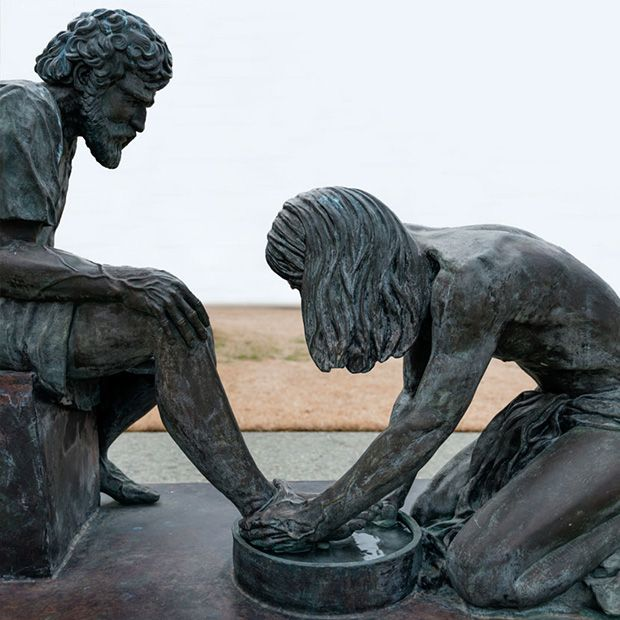 Bronze statue of Jesus Christ washing the feet of one of his apostles, an example of the charity.