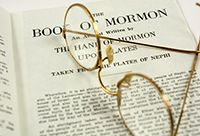 A pair of glasses sitting atop an open Book of Mormon.