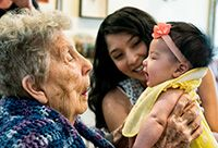 A grandmother cooing over her newborn granddaughter.
