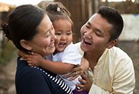 Two loving Mongolian parents doting on their baby girl.