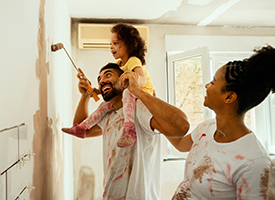 A young family painting a wall in their home.