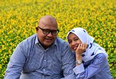 A husband and wife smiling together in a field of flowers.