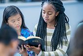 Two teenaged girls reading The Holy Bible.