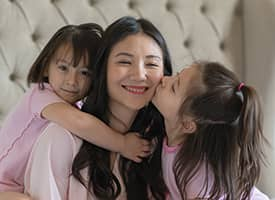 Two young girls hugging and kissing their mother.