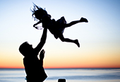 Silhouette of a young girl being tossed into the air by her father.