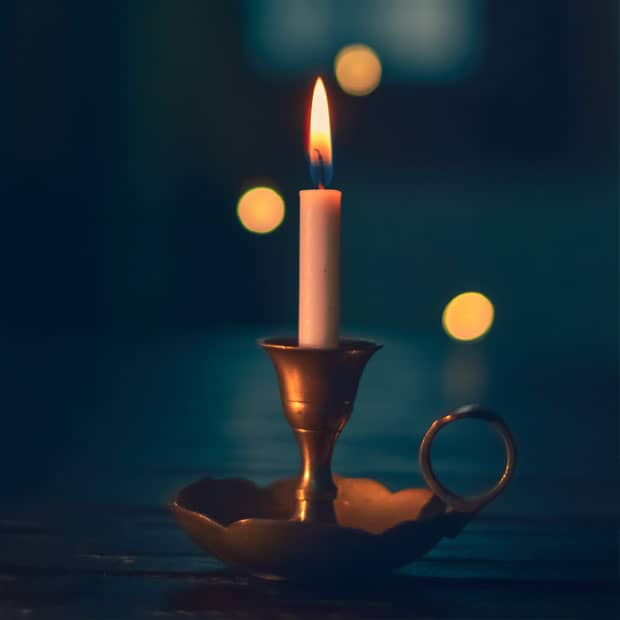 a candle burns, representing the guiding light of Jesus Christ
