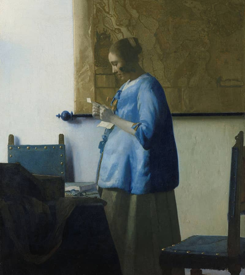 A woman in blue reads a letter