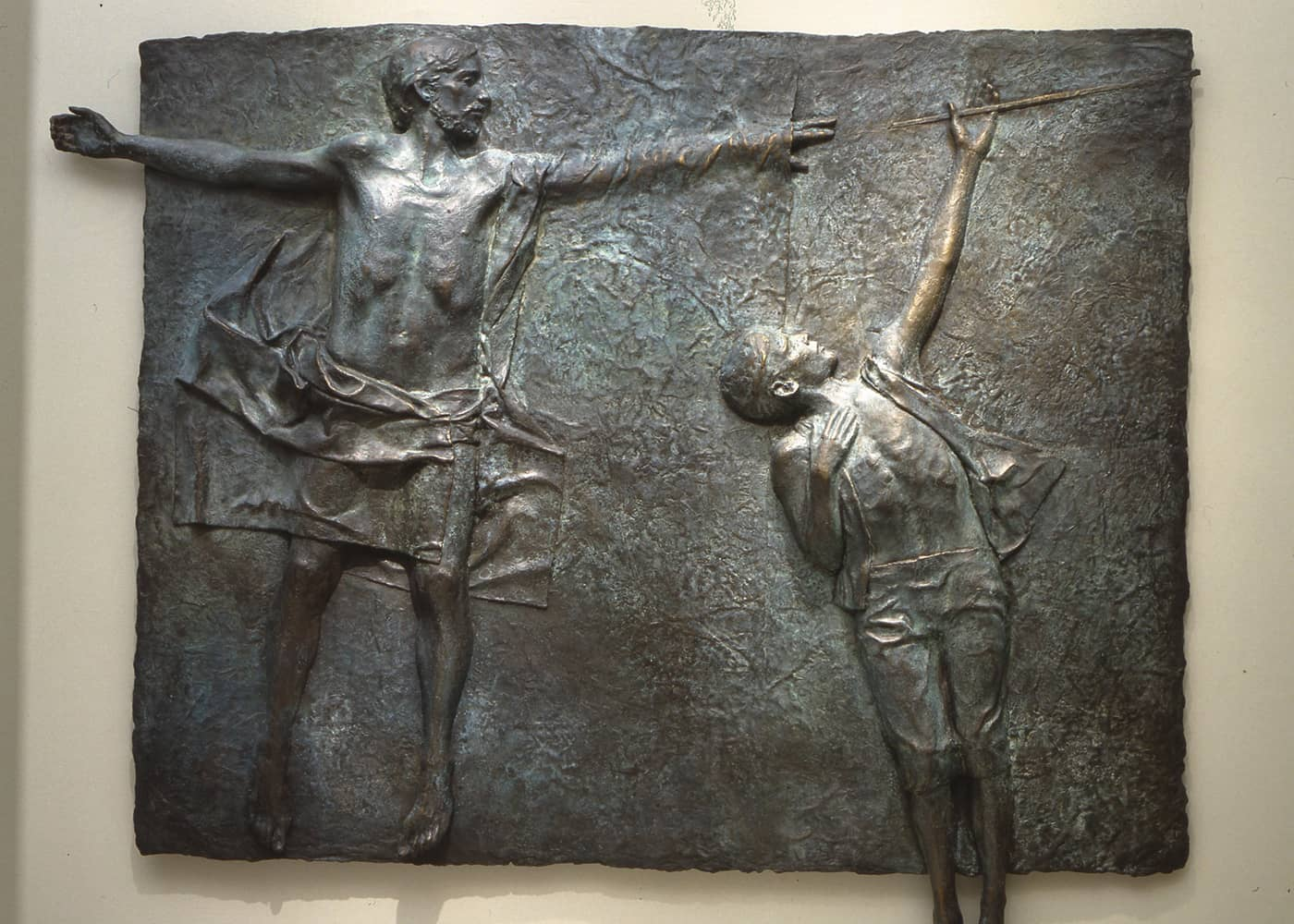A metal art piece depicting a boy reaching out to an iron rod, with help from Jesus Christ