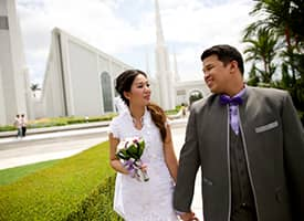 A newlywed couple walking on temple grounds