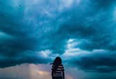 Woman standing in front a oncoming storm