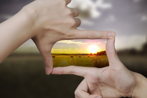 A sunset framed by two hands