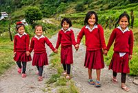 5 young Nepalese girls wearing red hold hands and walk down a gravel road