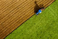 An aerial view of a tractor plowing a lush, green field