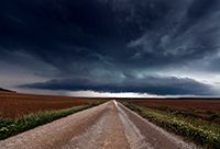 A long dirt road stretches to the horizon, where a large storm is brewing