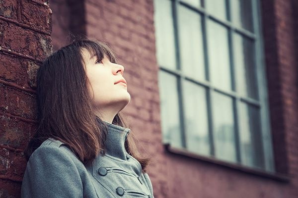 Girl standing against brick wall and looking up