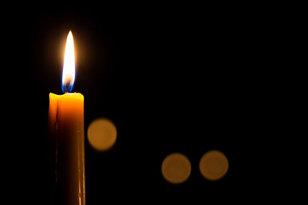 Single tall lit candle with a black background