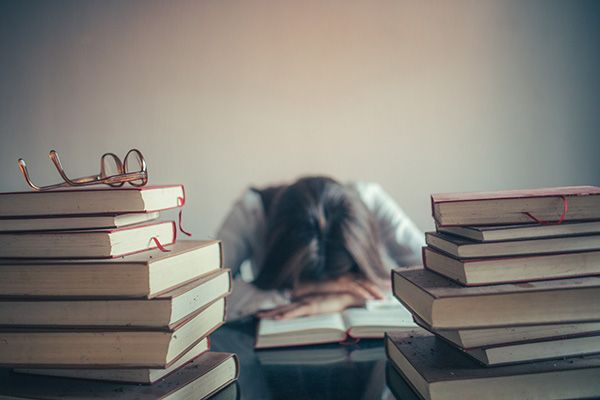 Female student laying her head on her desk, surrounded by books.
