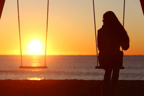Woman on a swing at the beach during sunset