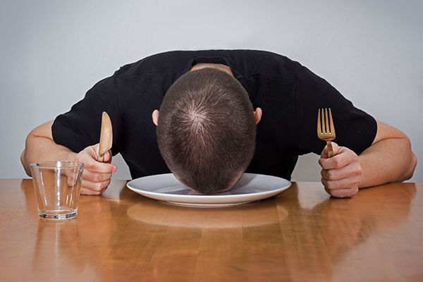 Hungry man, laying his head on an empty plate, holding a fork and knife in each hand.