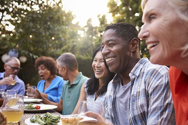 Adult friends gather for an outdoor picnic