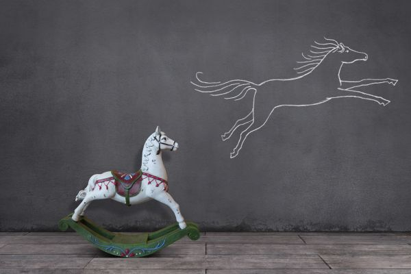 Side view of wooden rocking horse on wooden floor with running horse sketched on the wall.