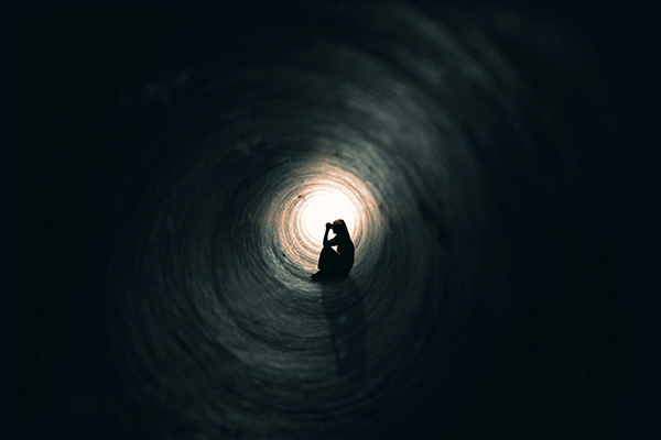 Woman praying in a tunnel