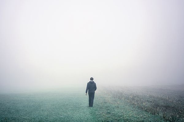 A solitary man walks on a green pasture into fog
