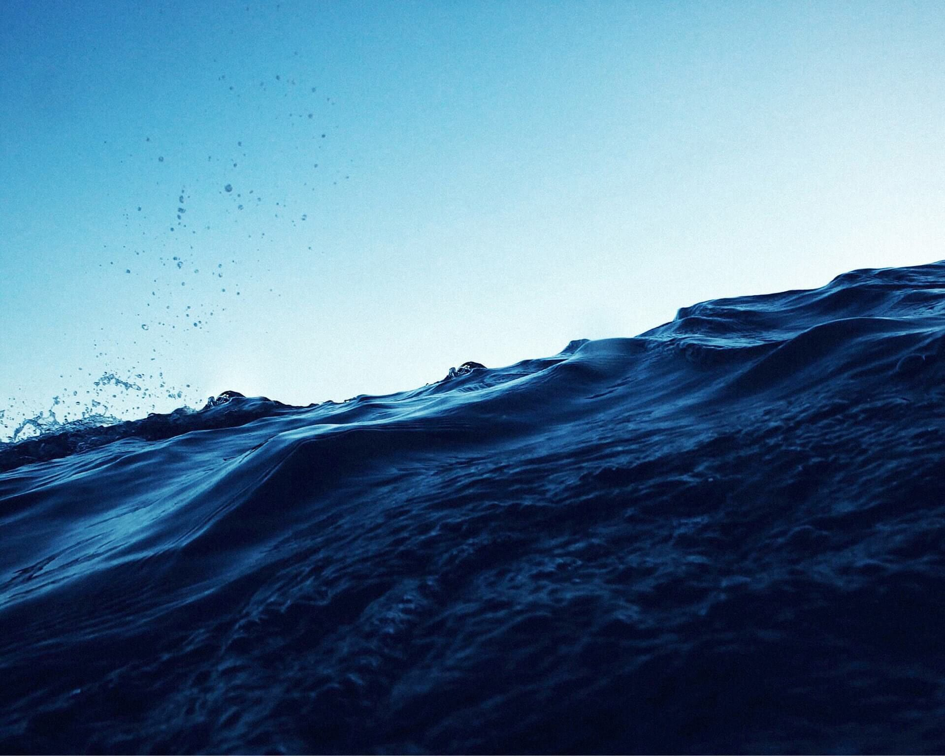 Photo of a deep blue ocean wave against the sky